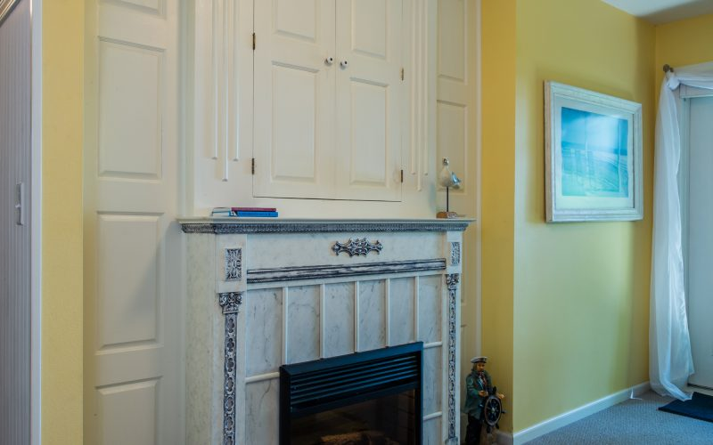 The fireplace in Hidden Harbor has a white surround with traces of blue details.