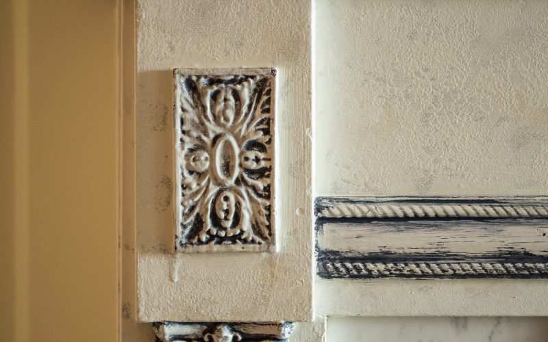 Details of the scrollwork on the white fireplace mantle that have been highlighted with blue accents.
