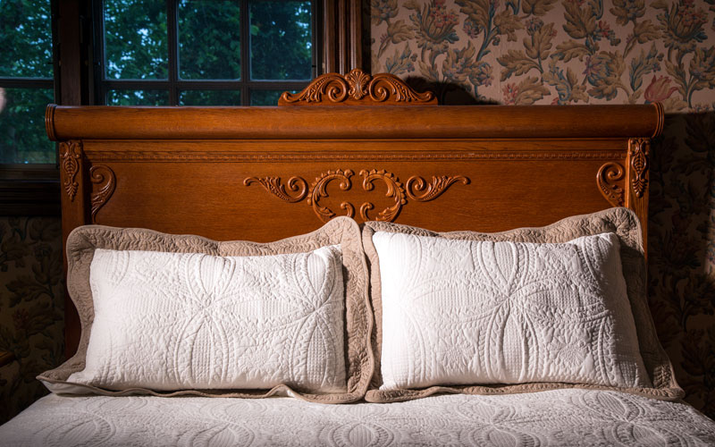 Antique queen bed in Cozy Corner with a beautiful quilt and matching pillow shams