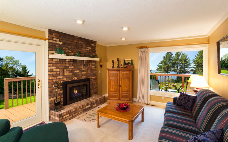 The Northwoods room has a suite with a large sitting area that includes a sofa, overstuffed chair and gas fireplace. There is a large picture window with a view of Lake Wissota and a patio doors leads to the deck and a patio area.