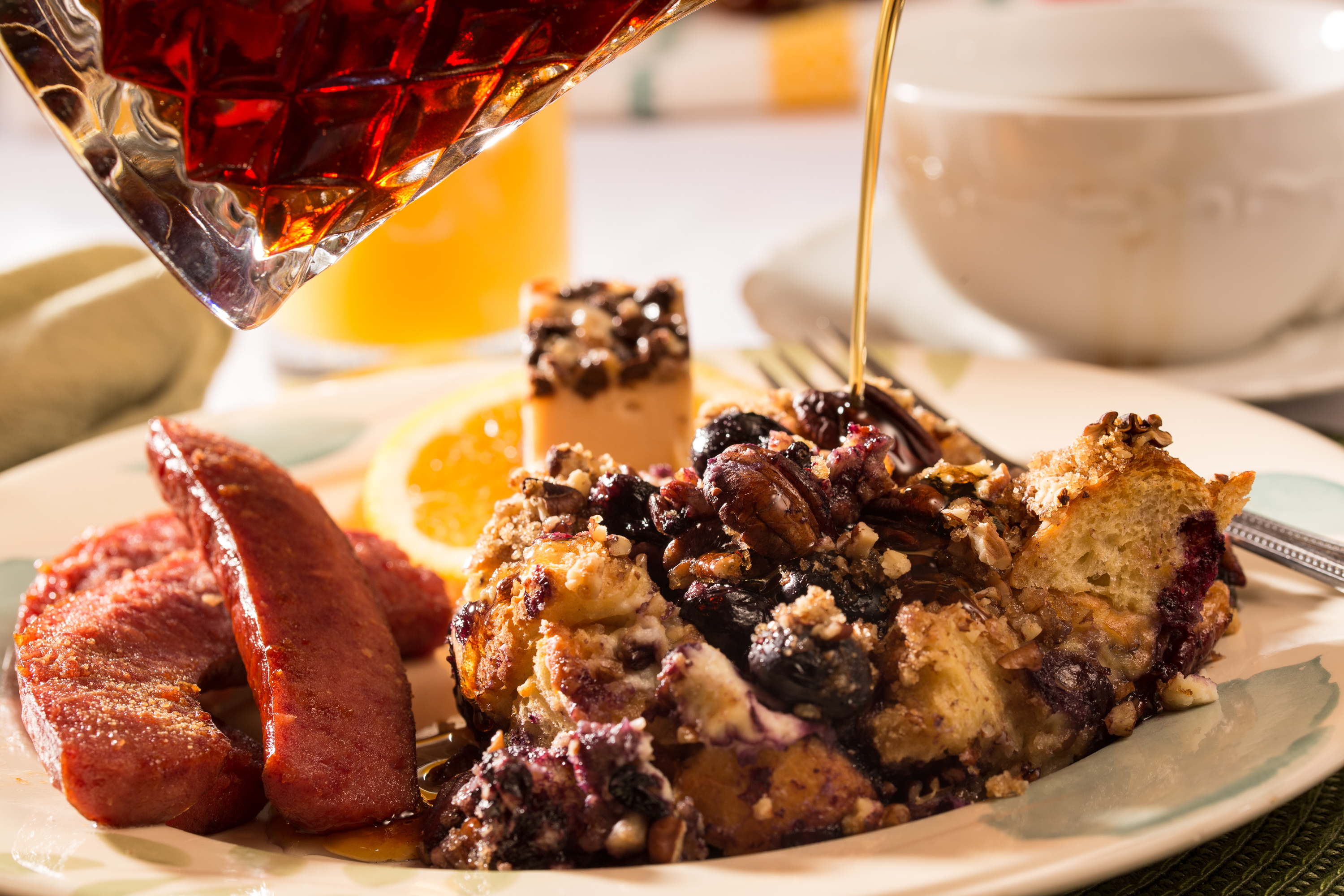 A breakfast of smoked sausage served with blueberry french toast bake. Maple syrup is being drizzled over the french toast.