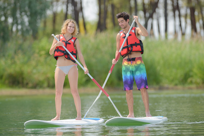 A Couple Stand Up Paddleboarding