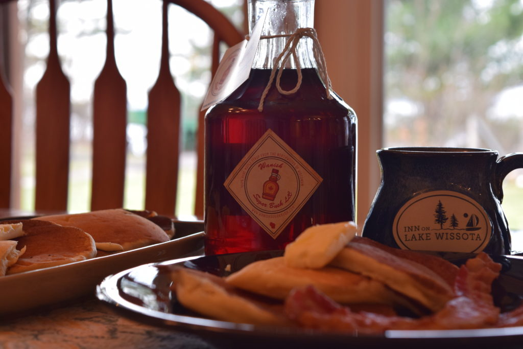 A bottle of Wanish Sugar Bush Maple Syrup on the table next to an Inn on Lake Wissota coffee cup and a breakfast plate of pancakes and bacon